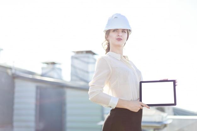 Hermosa businesslady en blusa blanca, reloj, casco y falda negra se paran en el techo y muestran tableta vacía