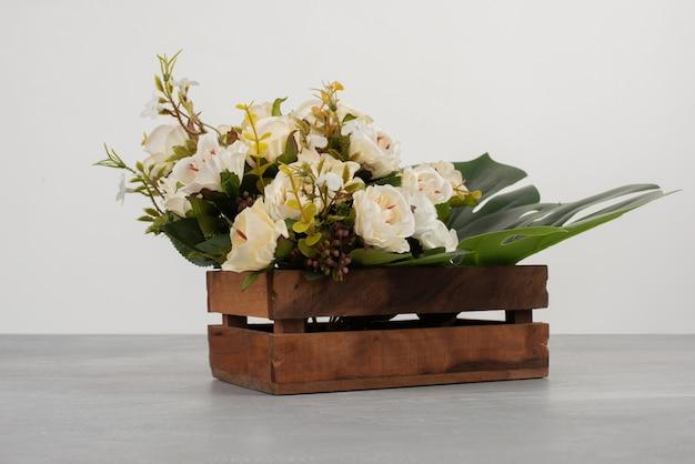 Hermosa caja de madera de rosas blancas sobre superficie gris