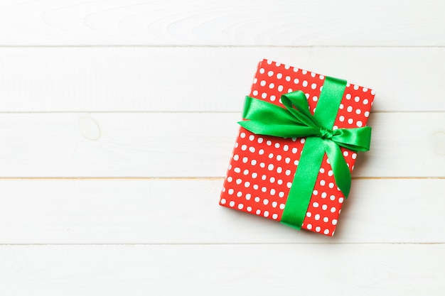 Hermosa caja de regalo con un lazo de color sobre la mesa de madera blanca.