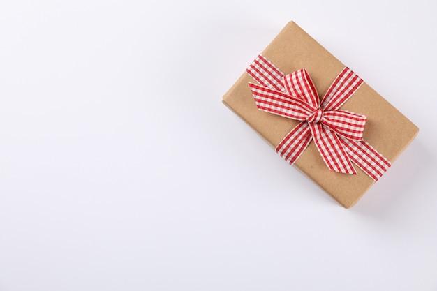 Hermosa caja de regalo con lazo a cuadros sobre fondo blanco, espacio para texto