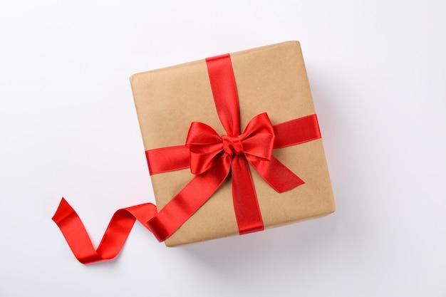 Hermosa caja de regalo con lazo rojo sobre fondo blanco, espacio para texto