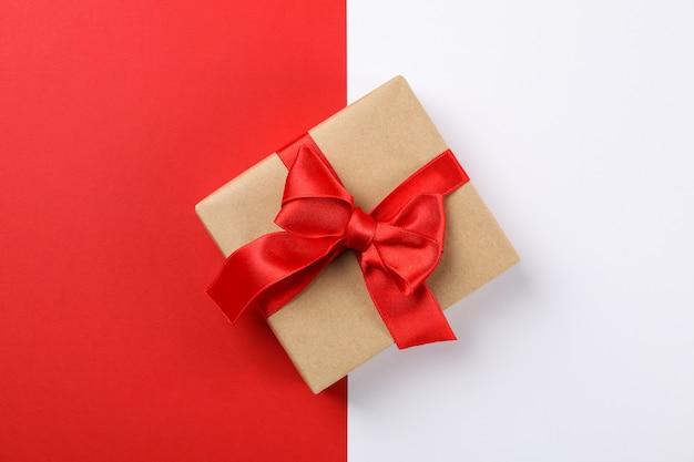 Hermosa caja de regalo con lazo rojo sobre fondo de dos tonos, espacio para texto