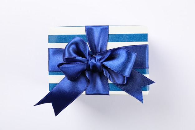 Hermosa caja de regalo con lazo sobre fondo blanco, espacio para texto