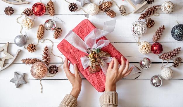 Hermosa caja de regalo rosa en las manos con el telón de fondo de los detalles de la decoración navideña de cerca.