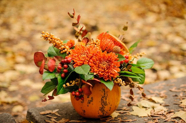 Hermosa calabaza con una composición de flores de otoño