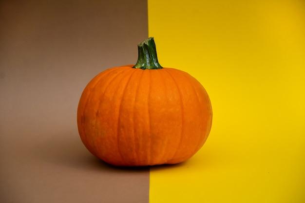 Una hermosa calabaza naranja se encuentra sobre un fondo marrón amarillento