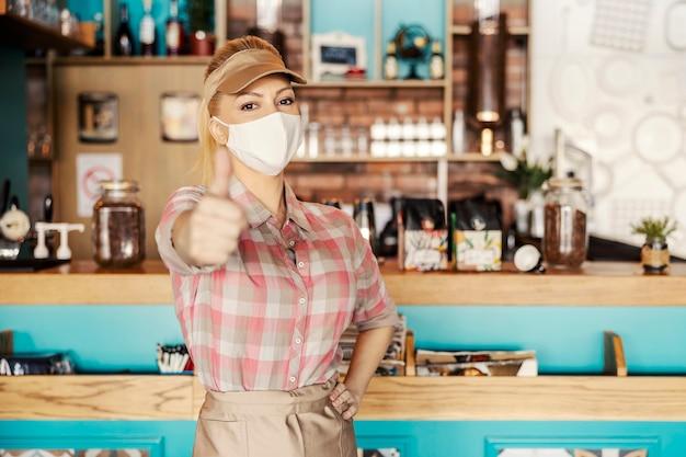 Hermosa camarera rubia en un uniforme con una máscara protectora facial muestra su pulgar hacia arriba con una mano mientras que la otra descansa sobre su cadera