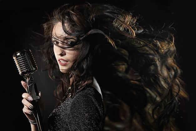 Hermosa cantante con micrófono y pelo ondeante.