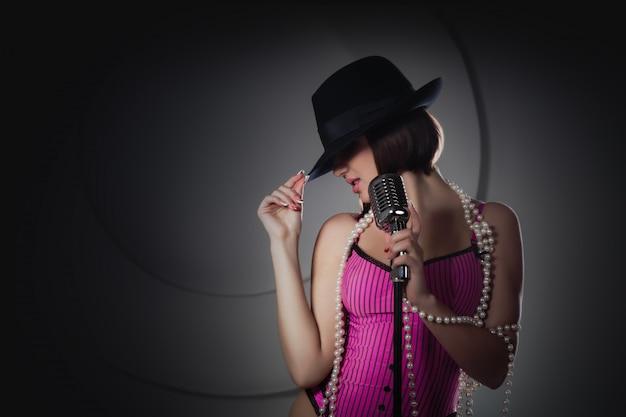 Hermosa cantante en sombrero negro cantando con un micrófono retro.