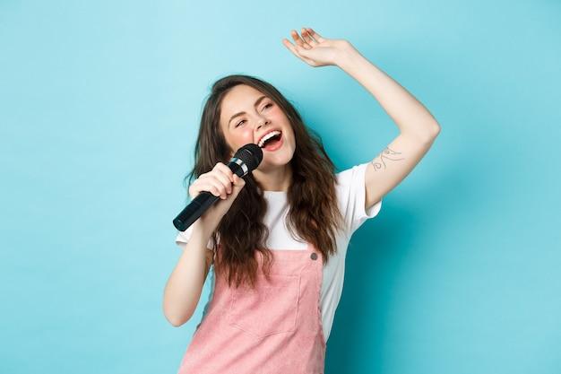 Hermosa cantante sosteniendo el micrófono, cantando karaoke en micrófono, de pie sobre fondo azul.
