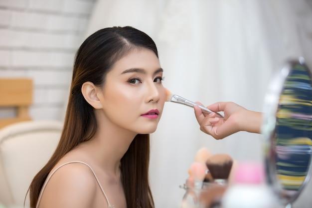 Hermosa cara de mujer y mano de maquillaje.