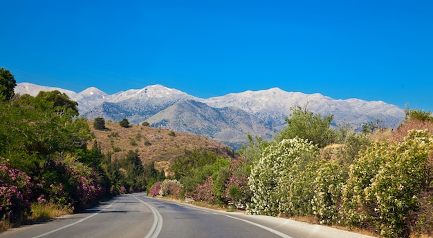 Hermosa carretera rural en creta con montañas sobre un fondo