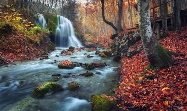 Hermosa cascada en el bosque de otoño en las montañas de crimea al atardecer