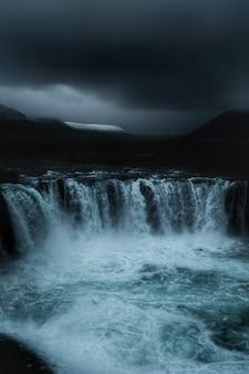 Una hermosa cascada en un campo con cielo oscuro