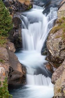 Hermosa cascada de velo velo, rocas cubiertas de musgo