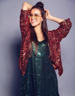 Hermosa caucásica sonriente hipster mujer morena modelo en brillante brillante que refleja la elegante chaqueta de verano y el vestido verde posando en gris