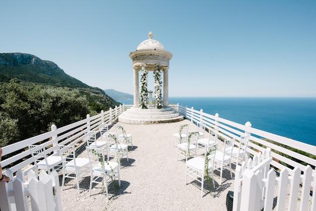 Hermosa ceremonia de boda blanca en la montaña junto al mar
