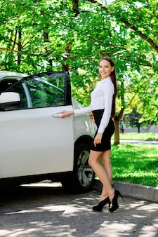 Hermosa chica abre la puerta de su auto y se va a sentar en el asiento del conductor