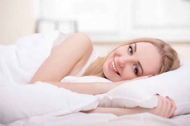 Hermosa chica acostada en una cama en su habitación.