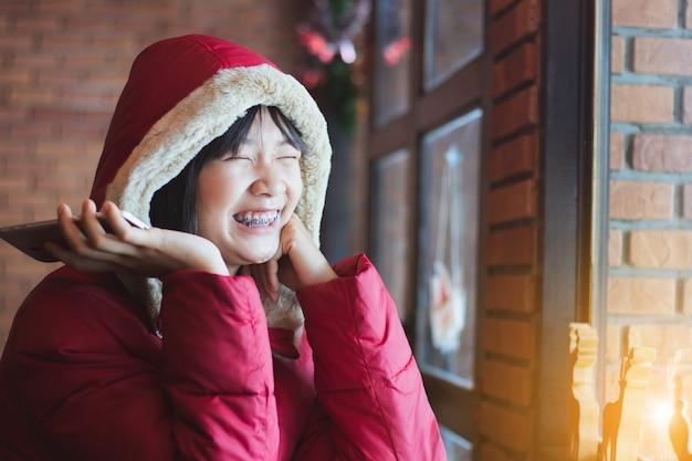 Hermosa chica adolescente asiática con teléfono inteligente