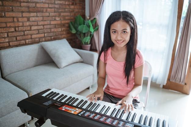 Hermosa chica adolescente asiática tocando un instrumento de piano