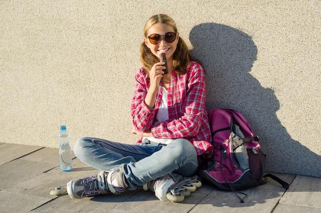 Hermosa chica adolescente calzada en rodillos toma chocolate.