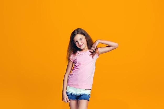Hermosa chica adolescente mirando sorprendido aislado en naranja