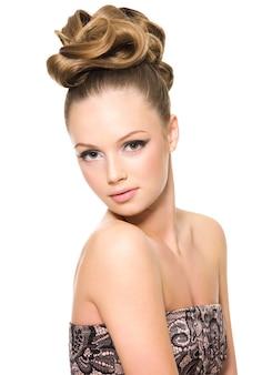 Hermosa chica adolescente con peinado rizado y maquillaje brillante - en espacio en blanco