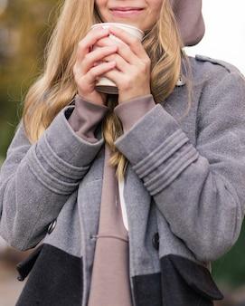 Hermosa chica adolescente en ropa de abrigo tiene un vaso con una bebida caliente en sus manos. foto