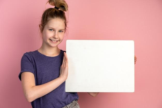 Hermosa chica adolescente rubia con ojos azules sostiene una hoja de papel en blanco sobre una pared rosa y sonríe