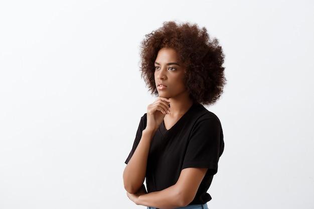 Hermosa chica africana pensando sobre la pared de luz.