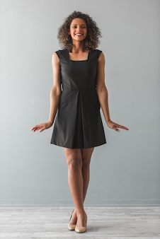 Hermosa chica afroamericana en vestido de cóctel negro.