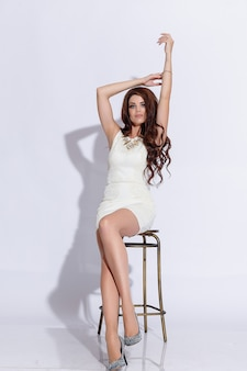 Hermosa chica aislada sobre fondo rosa. de pie, mirando a la cámara. vestido y zapatos blancos. hermoso peinado y maquillaje. chica morena con el pelo largo y recto negro volando. cabello magnífico.