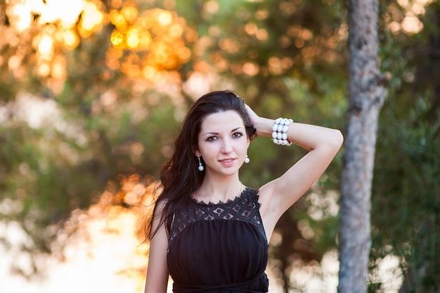 Hermosa chica al atardecer. foto de estilo de vida atmosférico al aire libre de una joven bella dama. cabello y ojos oscuros. otoño calido. primavera cálida. verano cálido.