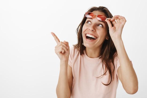 Hermosa chica alegre con gafas de sol posando contra la pared blanca