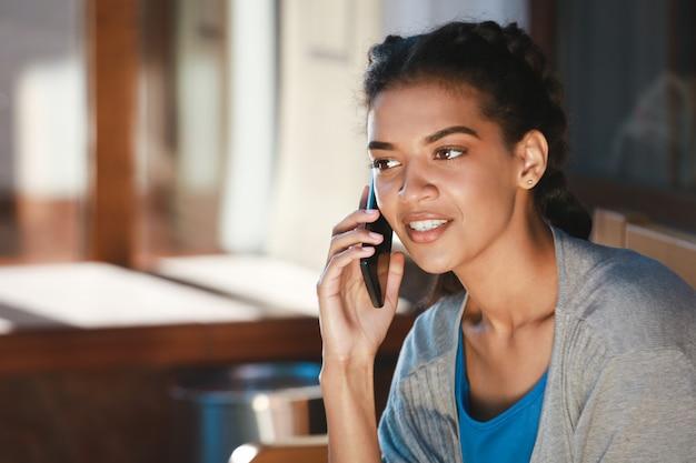Hermosa chica alegre de piel oscura hablando por teléfono