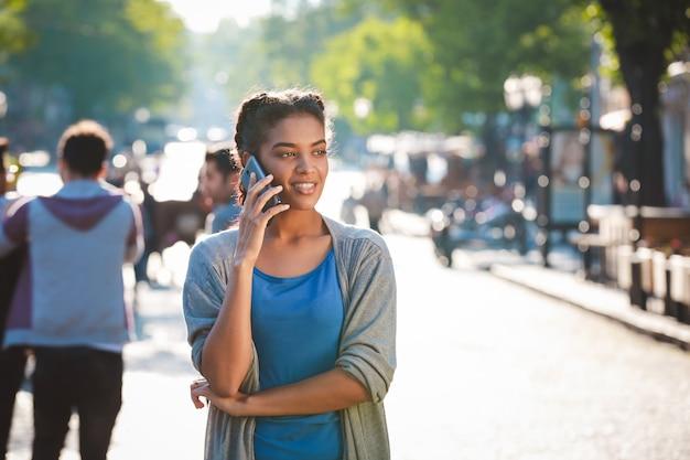 Hermosa chica alegre de piel oscura habló por teléfono