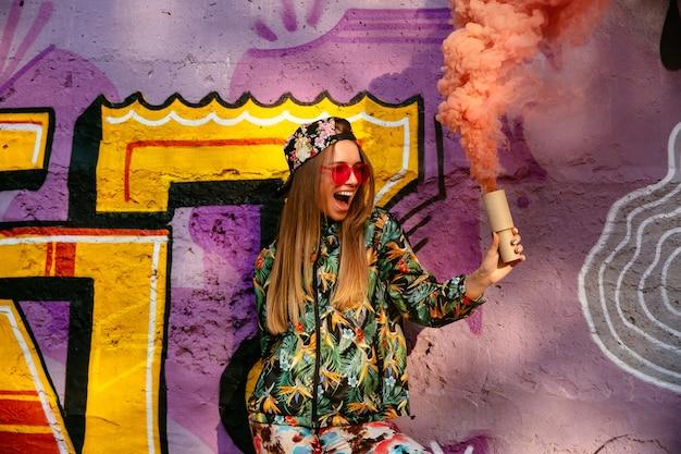 Hermosa chica alegre en ropa elegante colorido con humo bengala, que se divierte tiempo
