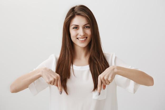 Hermosa chica apuntando con el dedo hacia abajo para mostrar el anuncio, sonriendo feliz