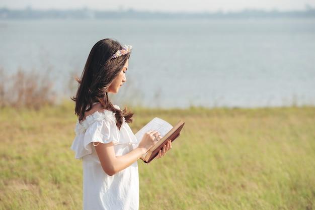 Hermosa chica de asia en el campo de hierba leyendo un libro cubierto