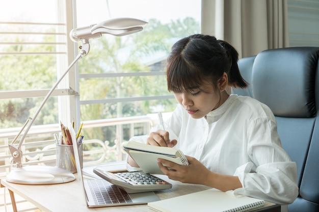 Hermosa chica asiática aprender haciendo la tarea, notas cortas con calculadora para estudiar en