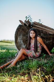 Hermosa chica asiática con cabello largo se sienta en la hierba cerca de un tocón de cabaña grande
