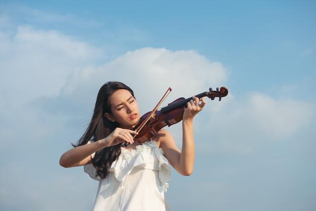 Hermosa chica asiática con cabello negro y vestido blanco tocando un violín