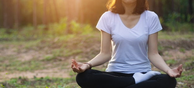 Hermosa chica asiática está meditando.