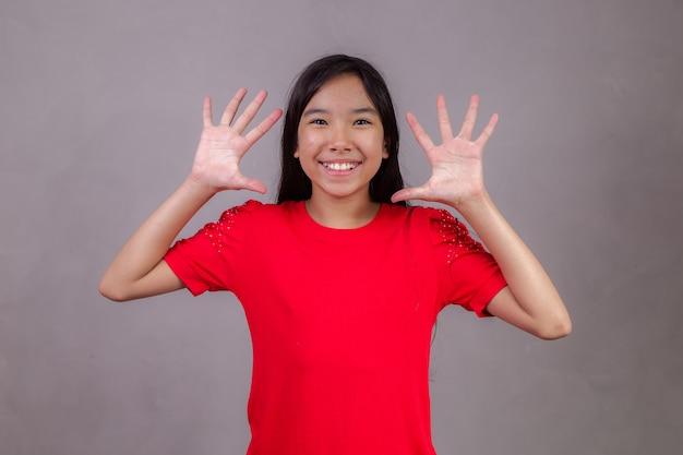 Hermosa chica asiática mostrando las manos
