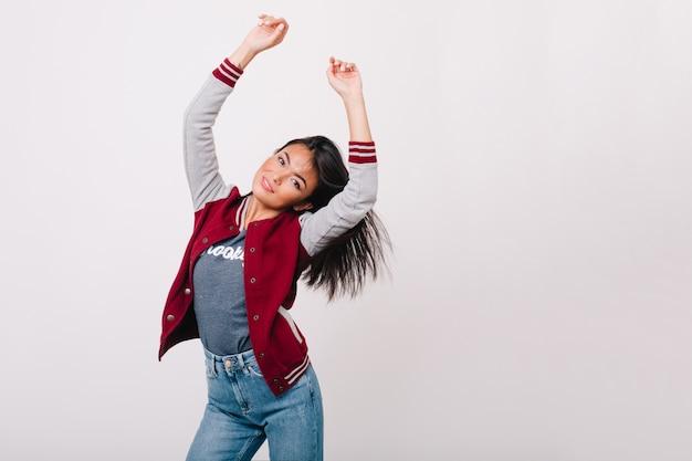 Hermosa chica asiática con piel ligeramente bronceada feliz bailando en la sala de luz. adorable modelo de mujer en jeans con pelo negro lacio divirtiéndose frente a la pared blanca.