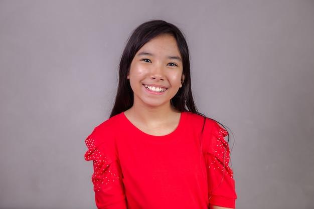 Hermosa chica asiática sentada sobre fondo gris. feliz niña asiática sonriendo.