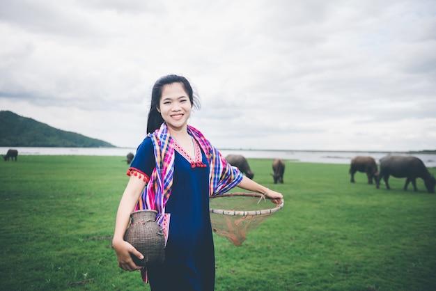 Hermosa chica asiática con trampa para peces y canasta, prepárate para pescar caminando en el campo cerca del lago en el campo de tailandia