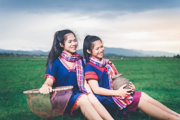 Hermosa chica asiática con trampa para peces y cesta, descansando después de la captura de peces, sentado en el suelo en el campo cerca del lago en el campo de tailandia