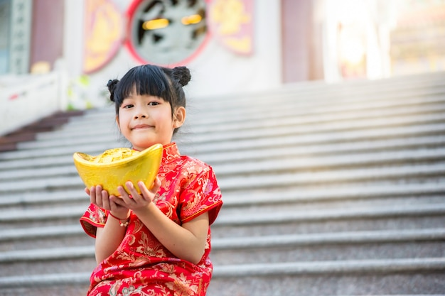 Hermosa chica asiática usa cheongsam rojo y sostiene lingotes de oro chino frente a los escalones de mármol del hermoso templo chino para el año nuevo chino